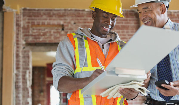 Construction workers reviewing contractual risk transfer plan