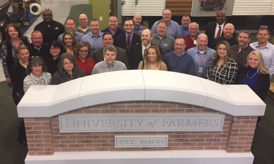 Group of Agents posing behind a University of Farmers Sign