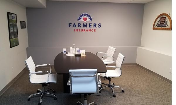 A meeting table below a Farmers logo in a conference room.