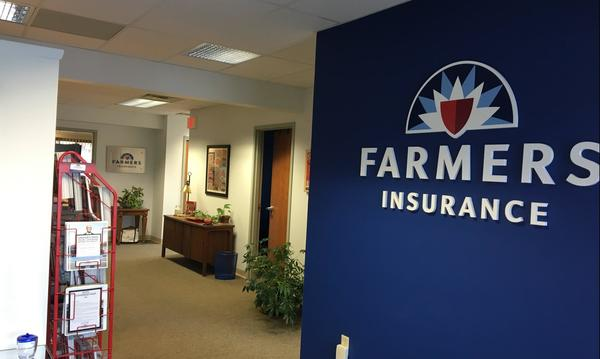 A hallway within Agent Joyce Felder's office, featuring the Farmers Insurance logo on a blue wall.