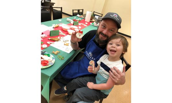 Man in Farmers Insurance hat and apron, decorating Christmas cookies at a table with a boy.