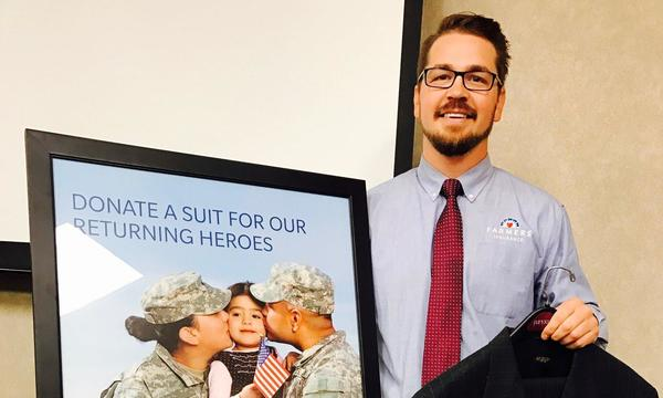 Jake in front of a suits for soldiers advertisement