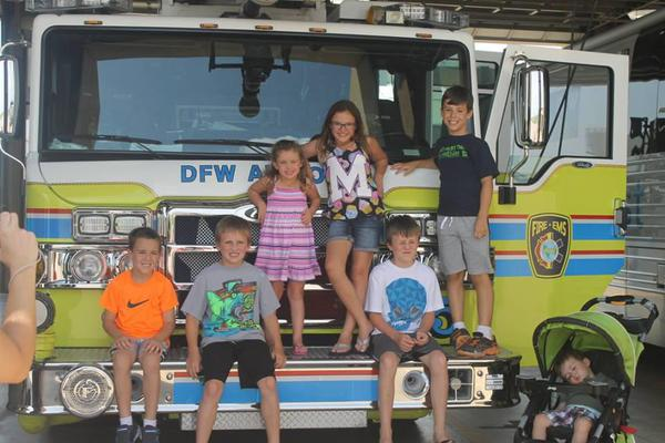 group of children sitting on a firetruck