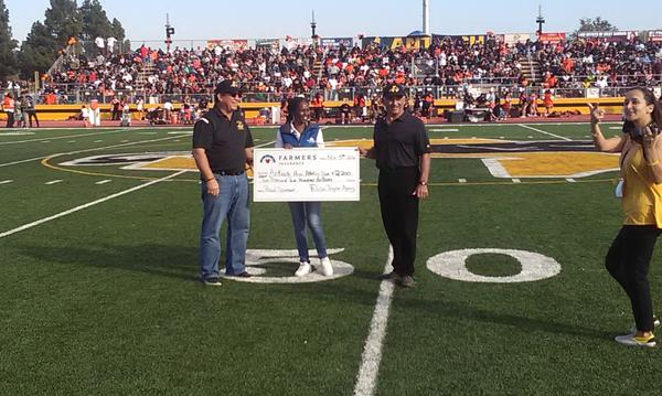 Agent Felicia Traylor presenting a check in the middle of a football field.