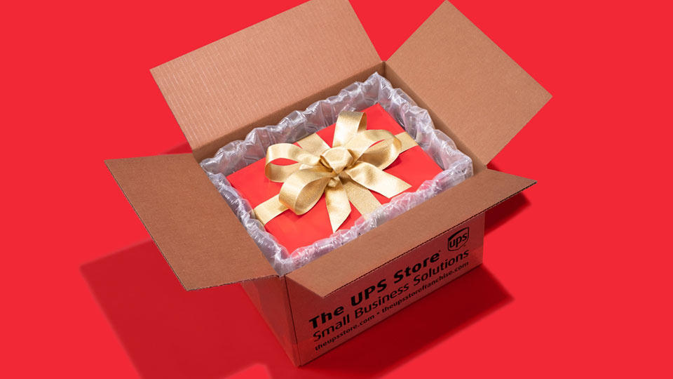 A red gift box wrapped in ribbon expertly packed in an open The UPS Store shipping box.
