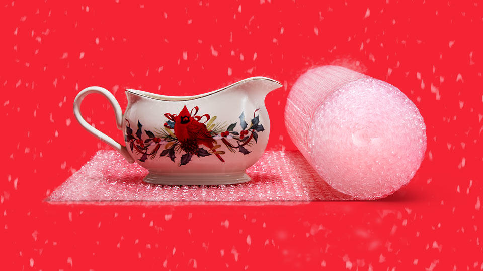 Image of a fragile gravy boat being packaged with bubble cushion on a red background with snow falling.