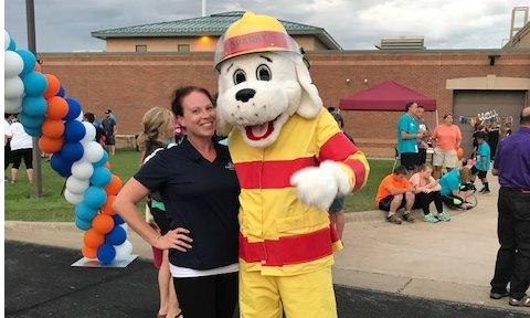 Farmers agent posing with firehouse dog mascot