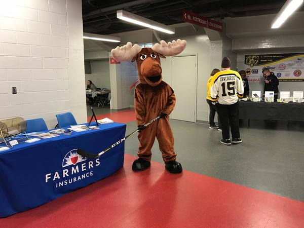 Moose mascot holding a hockey stick and standing in front of a Farmers booth