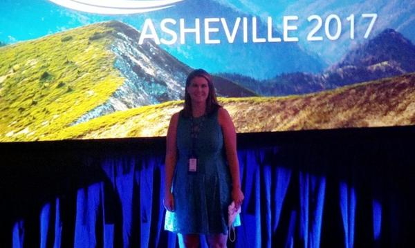 "Agent standing in front of a sign reading ""Asheville 2017"""