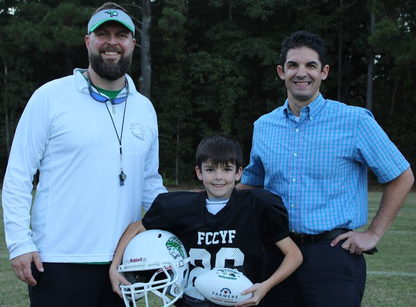 Coaches standing with young football player