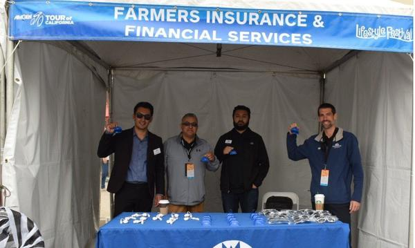 Agent and three men standing under a Farmers tent