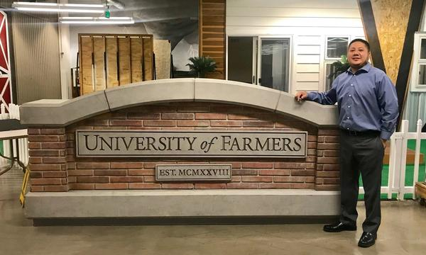 The Agent stands next to the sign for Farmers University