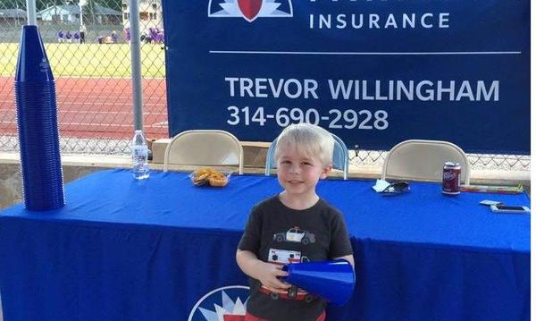 A young boy in front of a Farmers Insurance booth and table.