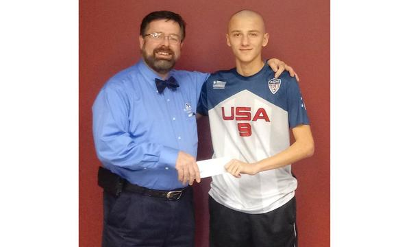 Agent standing with his arm around a young man both holding a check