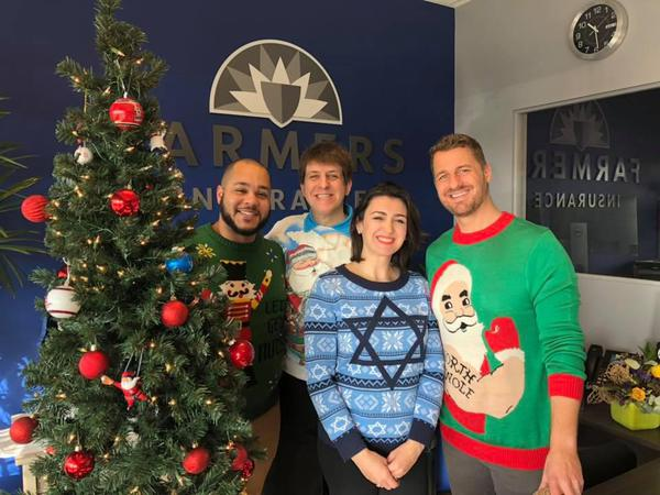 Agents taking a holiday photo by a tree in sweaters