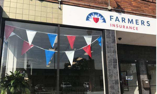 A Farmers storefront decorated with red white and blue flags