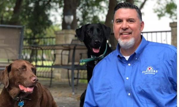 Agent Greg with a brown and black lab at a park posing for photo.