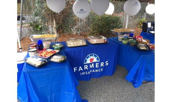 A blue Farmers Insurance table with food and balloons on it