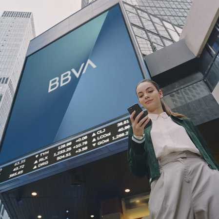 A woman on her phone stands in front of a skyscraper with a large BBVA USA Logo along the side