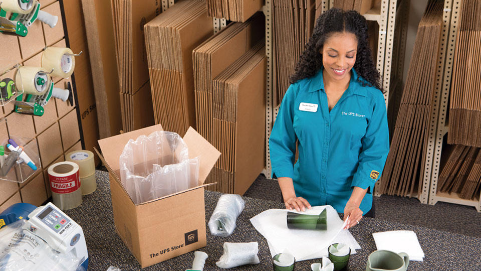 Employee wrapping and packing a glass for shipping