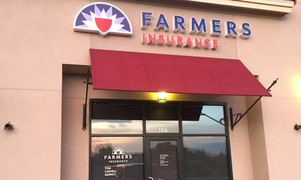Photo of the outside of our office with red awning and Farmers logo