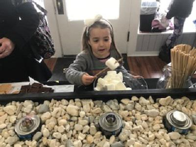 Little girl making s'more in office.