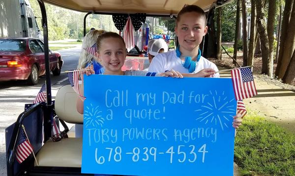 "Two children sitting on the back of a golf cart, holding American flags and a sign that reads, ""Call My dad for a quote! Toby Powers Agency 678-839-4534."""