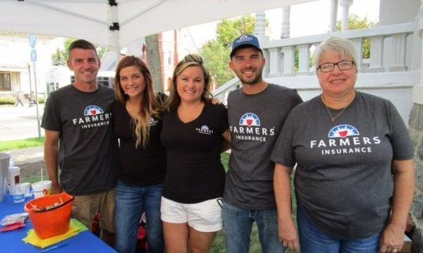 A group of people wearing Farmers Insurance® t-shirts pose under a tent