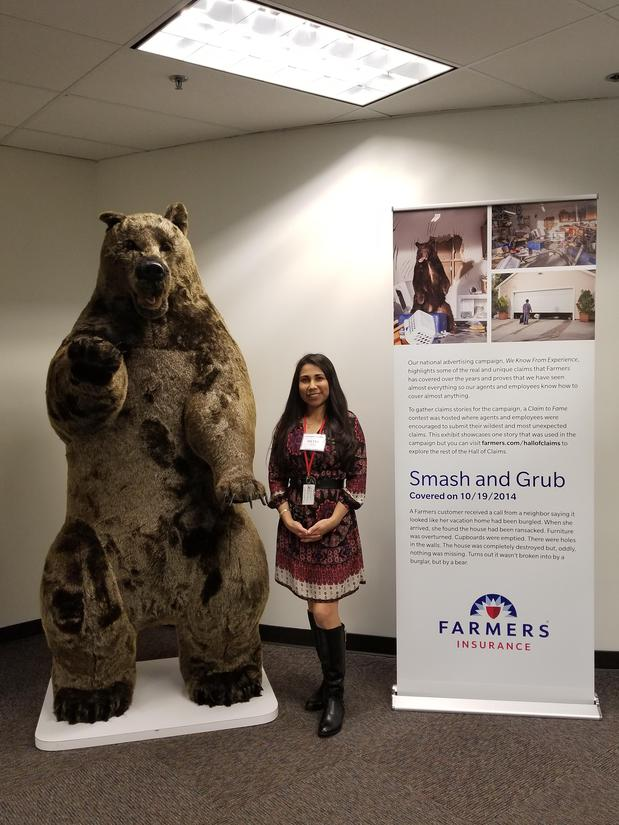 Agent standing next to large bear statue at Farmers University museum