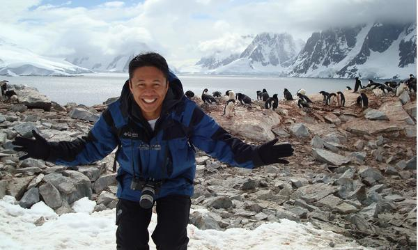 A man wears several coats standing in front of some penguins with mountains in the background