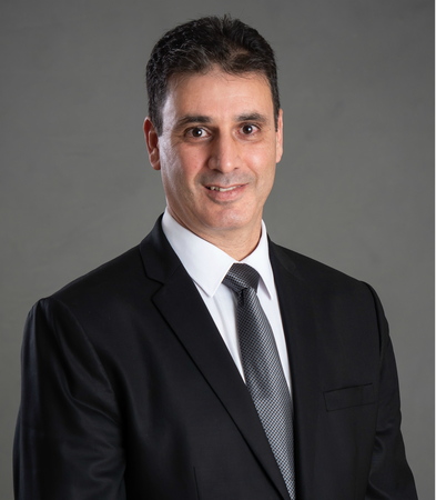 Male agent Nadir Mohli on a gray background.
