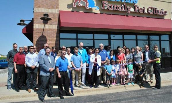 A large group of people stand in front of a pet clinic holding a big ribbon