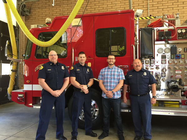 Agent Saed with three firemen in front of a fire truck