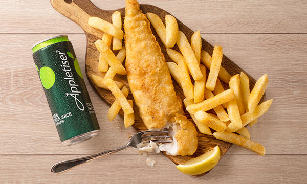 Crispy deep-fried fish and chips with a slice of lemon and an Appletiser served on a wooden board.