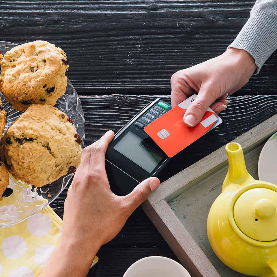 Top-down image of a contactless card payment at a counter with tea and scones