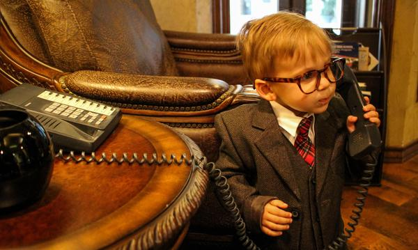 Little boy in suit on telephone.