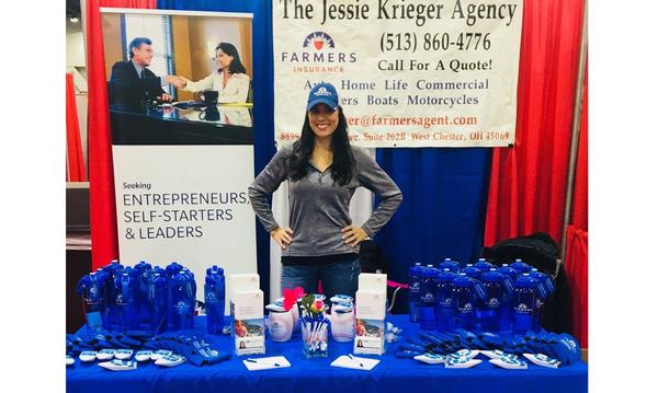 The agent stands behind a Farmers insurance booth at a busy event