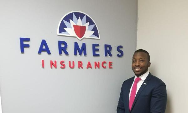 Man in suit poses in from of Farmers Insurance logo