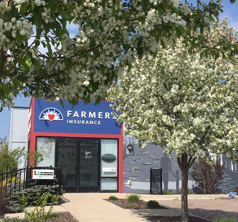 Exterior photo of Farmers insurance office surrounded by green tree and shrubbery.