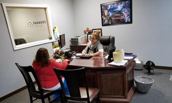 An Arnold Alaniz Agency female staff member sitting behind her desk, speaking with a customer.