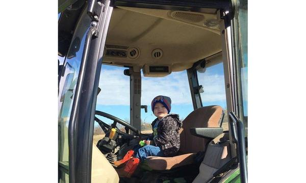 Young boy sitting behind the wheel of a tractor