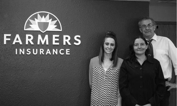 Agent standing with two women in front of the Farmers Insurance logo