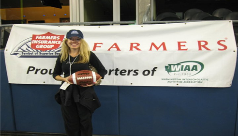 Isabelle holds a football and poses in front of a Farmers Insurance banner