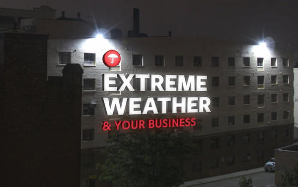 "A night image with text across a building stating ""Extreme Weather and your business""."