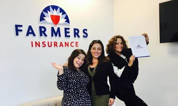 Farmers agent posing with friends in front of Farmers logo