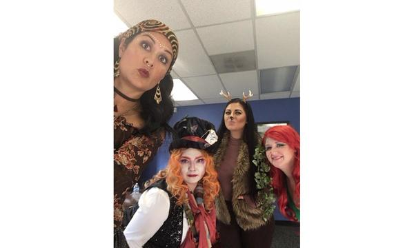 4 female staff members dressed in costumes for halloween