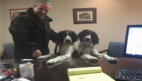 Farmers Agent Doug Blasing with two large dogs