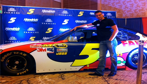 Elijah Duloglo posing next to a No.5 Farmers race car.