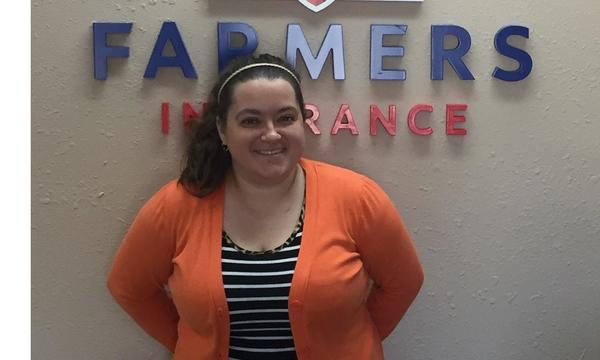 Marty Mcbride Agency female employee standing in the office in front of the Farmers logo.
