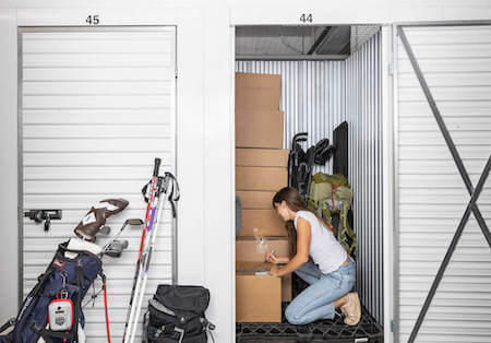 Woman labels boxes in her storage unit containing camping gear, skiis, golf clubs, boxes and more